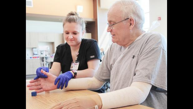 Bruce Heilesen works with Inpatient Occupational Therapist Maddie Krueger (above) and Inpatient Physical Therapist Alison Mooney (right) to regain his mobility after 12 percent of his body was burned in an accidental fire caused by a propane tank. (