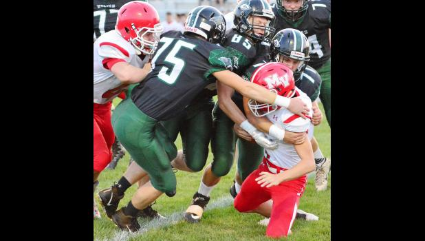 IKM-Manning defenders Dane Blom (75), Marshall Hansen (85) and Austin Ahrenholtz (71) take down a Missouri Valley ball carrier during Friday's game. Also pictured is Chris Monson (74).