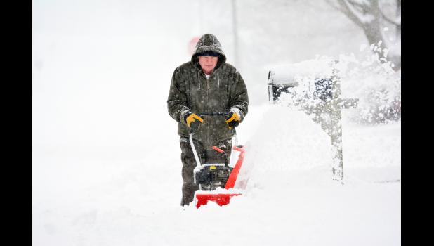 Jerry Lambert tried to get through a drift along his sidewalk Friday morning.  Lambert said it's good it wasn't cold, and the wind was the worst culprit making the drifts larger.