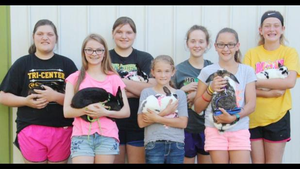 The kids participating in the rabbit agility course hold their rabbits following a meeting. Front row, left to right: Emily Taggs, Addison Obrecht, Cori Mages. Back row, left to right: Madison Rivera, Kaylee Rivera, Allyssa Obrecht and Mallory Mulligan.