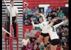 HCHS senior Brenda Hopkins (2) pushes the ball over the net against Red Oak Tuesday night as sophomore middle Olivia Petersen prepares to go on the attack. (Photos by Mike Oeffner)