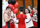 Harlan Community senior Carter Bendorf is presented with balloons and a congratulatory poster board from the cheerleaders after earning his 100th career win during Thursday's home wrestling meet. Left-right: Carter Bendorf, Katie Burchett, Jenna Gessert (holding sign), Jessalyn Schleimer, Emma Smith, Bailey Arnold and Kelsi Hoffman.