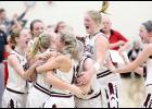 Exira-EHK freshman Mollie Rasmussen is hugged by senior Damian Peterson (12) and surrounded by teammates following her game-winning shot from the right corner that gave the Spartan girls a 59-57 victory over Ar-We-Va. (Photos by Mike Oeffner)