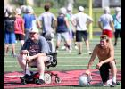 Longtime HCHS football coach Curt Bladt (left) watches from midfield along with senior Thomas Frederick during Tuesday's session of the Cyclone Camp of Champions. This year's camp (Aug. 5-9) - drew about 80 players in grades 9-12 and another 60 in grades 7-8.
