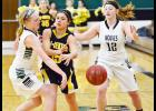 IKM-Manning senior Payton Sporrer (left) knocks the ball away from Tri-Center's Tristen Hughes as Shauna Reitan also defends. The Wolves finished the game with 23 steals.