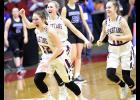 SURVIVE AND ADVANCE -- Exira-EHK players Shay Burmeister (22), Alisa Partridge and Quinn Grubbs celebrate as time expires in the Spartans' 60-55 state tournament quarterfinal win over MMCRU Wednesday afternoon. (Photos by Mike Oeffner)