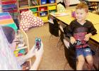Miranda Sorensen takes a photo of her son, Raiden, in his kindergarten room Tuesday evening at the back to school open house for the Harlan Community Schools.