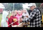 Bernie Schroder demonstrates rope making to students at Carstens Farm Youth Day last Friday.  L to R are Audrie Bruck, Levi Obrecht, Blake Bruck, Kaitlynn Schmitz, Braelin Behrens, Alex McCulley and Kobe Klaassen.