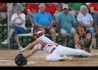 Boone pinch runner Kinsie Zinnel (4) dives toward home plate to score a fourth-inning run as HCHS catcher Madison Schumacher attempts to tag her out. The Toreadors scored 11 times in the fourth inning to beat the Cyclones 12-0 in Saturday's 4A regional semifinal.