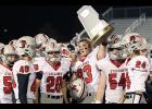 Jake McLaughlin holds up Harlan Community's Class 3A playoff quarterfinal trophy following Friday night's season-ending loss at Lewis Central. Also pictured are seniors Eli Boldan (24), Joey Arkfeld (54) and Brian Trevino (20), as well as junior Kobe Livengood (40).
