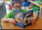 Xavier Rosmann, son of Daniel Rosmann and Ellen Walsh-Rosmann, looks up from reading his copy of My Family's Corn Farm by Katie Olthoff. The books in the My Family's Farm series highlight individual Iowa commodity farms and are written at a third-grade reading level.